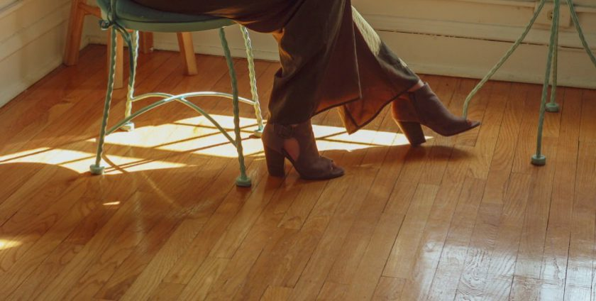 Woman setting her feet in heels on hardwood flooring